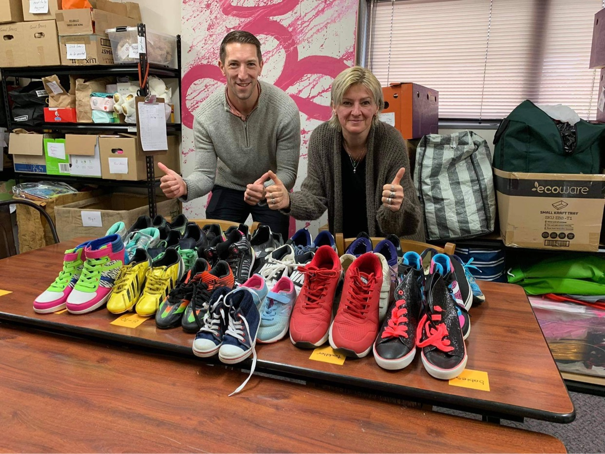 Two people with lots of donated sports shoes